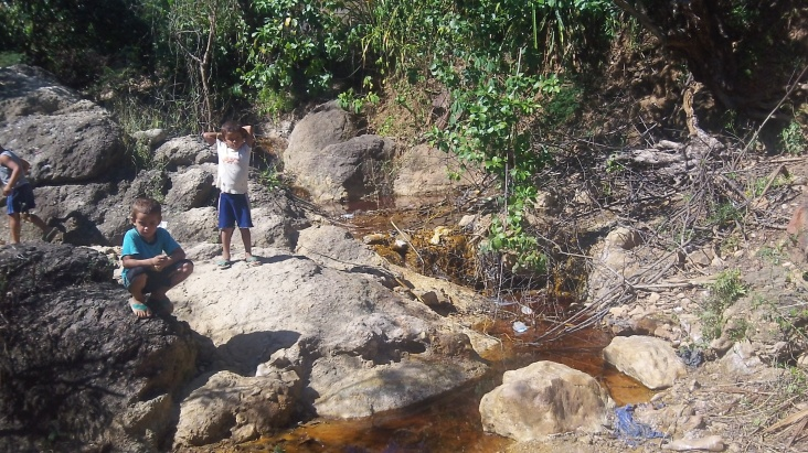 Two boys stand near a river in the department of La Unión, El Salvador, that residents say was left polluted by a U.S. mine. Credit: DM Mackey